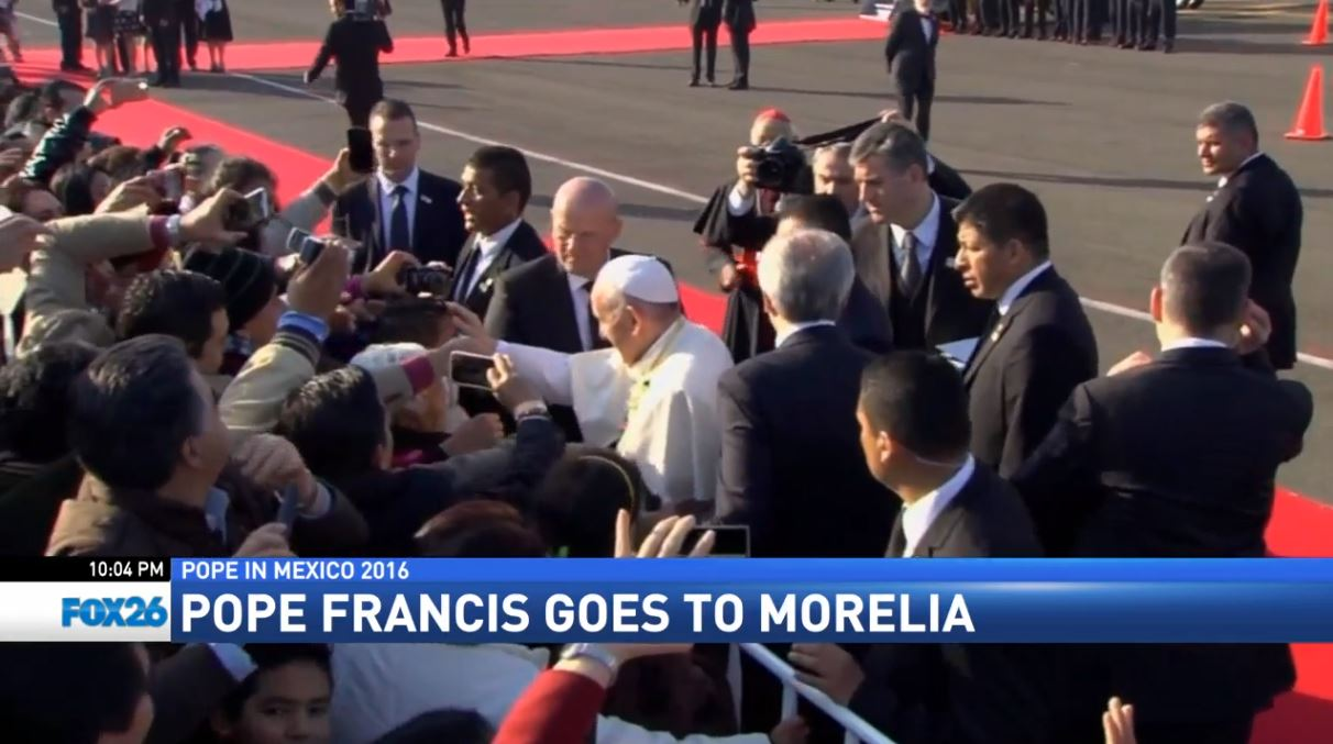 Pope Francis greeting spectators lining the streets of Morelia, Mexico