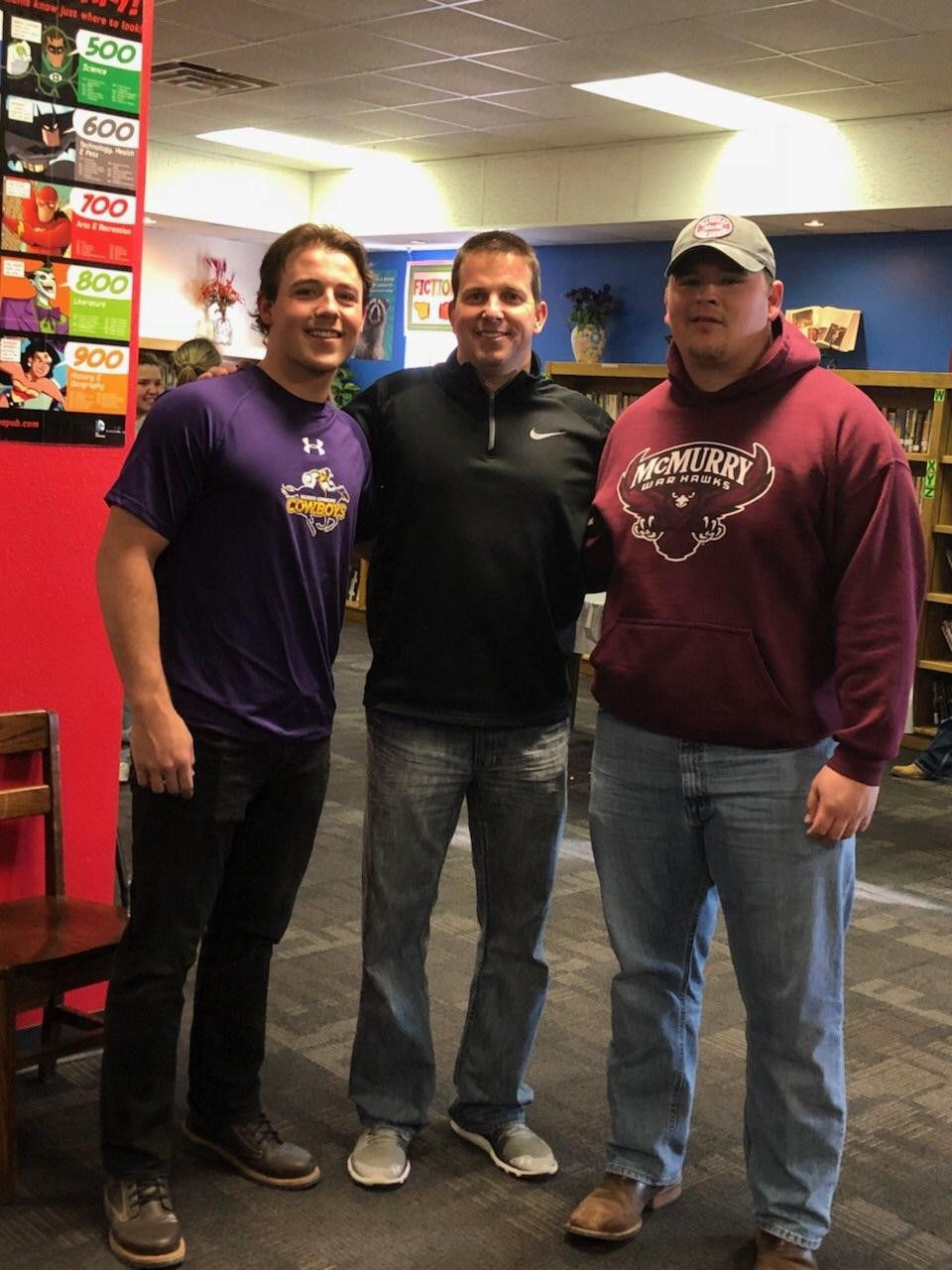Hawley's Quay Stokes and Kole Smith posing with Hawley athletic director and head football coach Mitch Ables during signing day.<p></p>