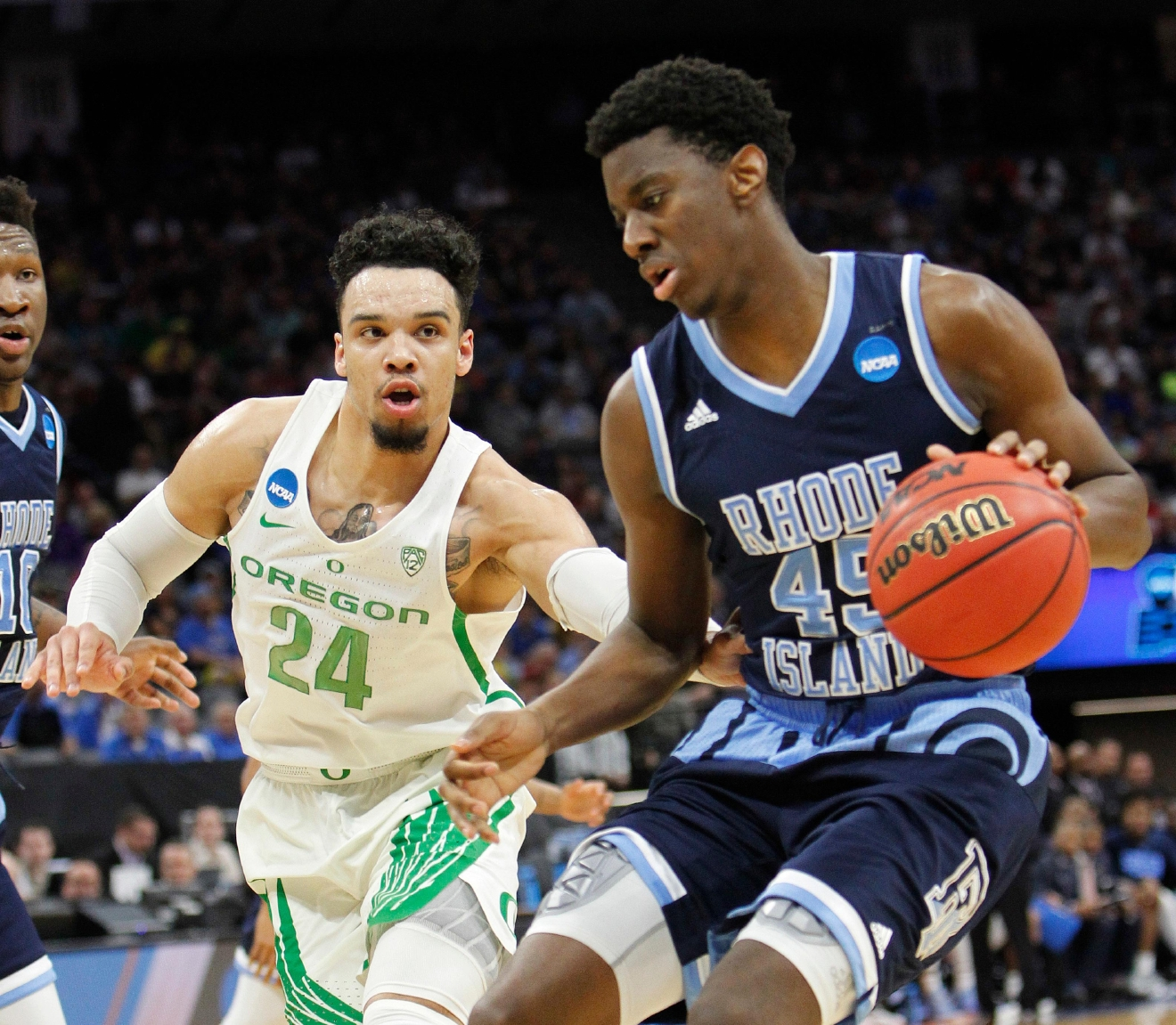 Rhode Island forward Nicola Akele, right, drives against Oregon forward Dillon Brooks during the first half of a second-round game of the men's NCAA college basketball tournament in Sacramento, Calif., Sunday, March 19, 2017. (AP Photo/Steve Yeater)