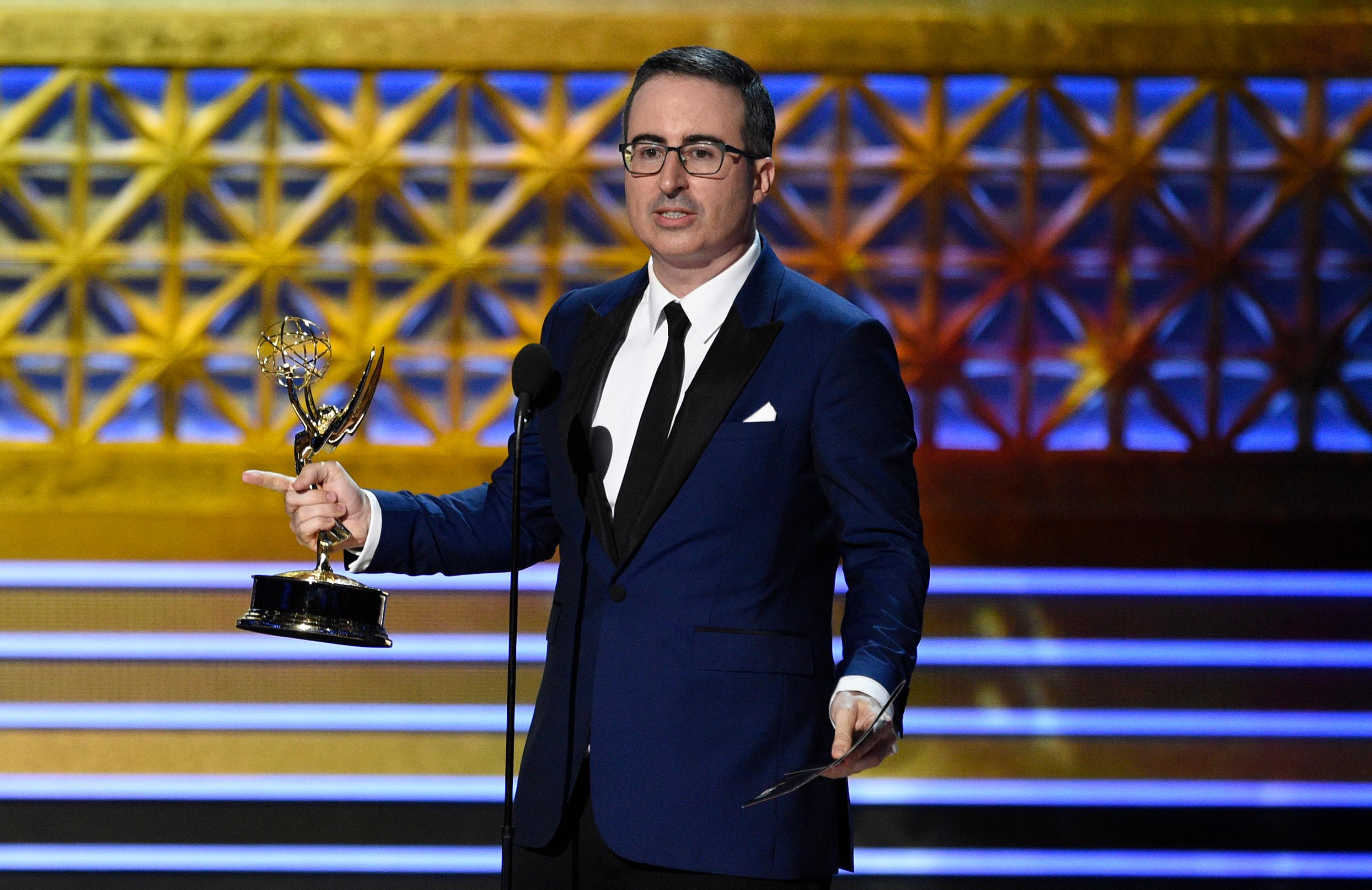 "John Oliver accepts the award for outstanding writing for a variety series for ""Last Week Tonight with John Oliver"" at the 69th Primetime Emmy Awards on Sunday, Sept. 17, 2017, at the Microsoft Theater in Los Angeles. (Photo by Chris Pizzello/Invision/AP)"